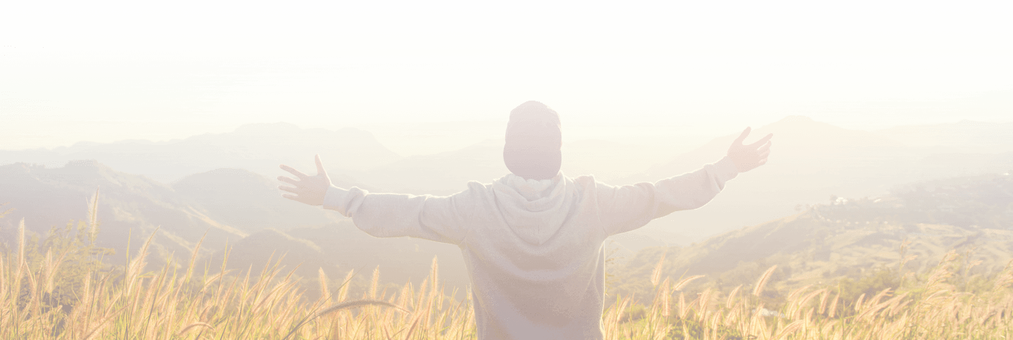 Man with arms stretched out looking out into the mountains