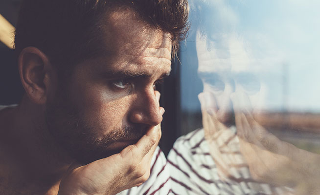 Depressed man looking out of a window