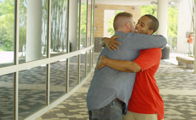 two men hugging for support