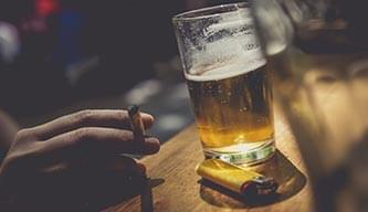 Smoking a cigarette at a bar with a beer and a lighter