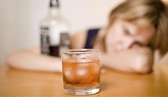Alcoholic woman with a bottle of liquor staring at a glass of whisky