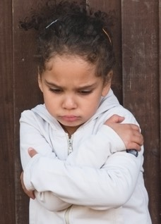 Young girl looking agitated, arms folded.