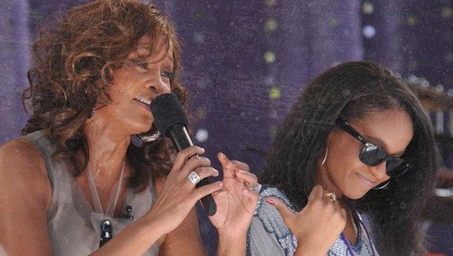 Whitney Houston singing on stage next to daughter Bobbi Kristina Brown in 2009