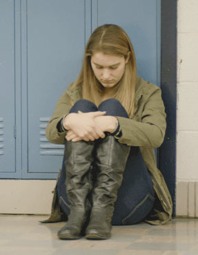 Young girl cradling legs in a school hallway.