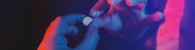 Person holding pill in their hands.