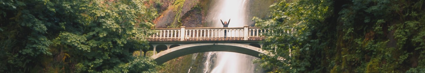 Person posing on walk bridge in front of waterfall
