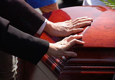 Family touching casket